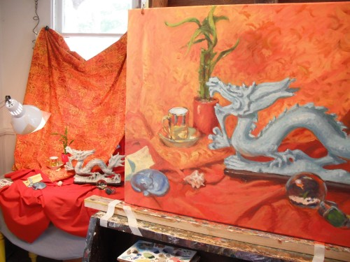 A view of the painting with the still life set up behind it.